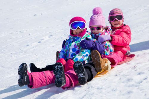 52754544 - group of kids riding on snow slides in winter time